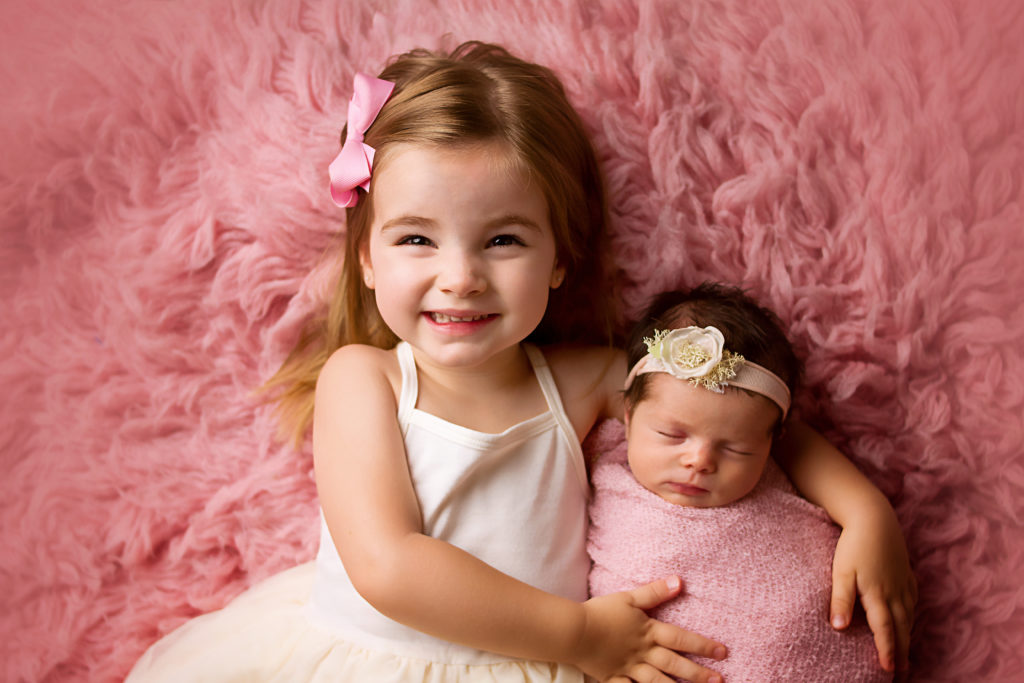 Older sister laying with baby sister on pink rug during her dallas newborn session with jessica
